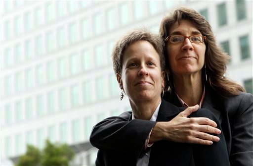 This Dec. 17, 2010 file photo shows Karen Golinski, right, hugging her wife Amy Cunninghis as they pose for a photograph outside of a federal court building in San Francisco. (AP Photo/Jeff Chiu, File)