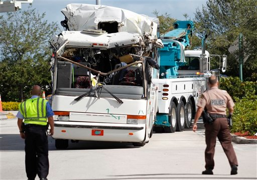© Law enforcement officers watch as a bus which hit a concrete overpass at Miami International Airport is hauled away, Saturday, Dec. 1, 2012 in Miami.