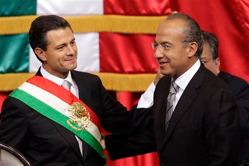 © Mexico's incoming President, Enrique Pena Nieto, left, smiles as he stands with outgoing President Felipe Calderon during the inauguration ceremony at the National Congress in Mexico City, Saturday, Dec. 1, 2012.