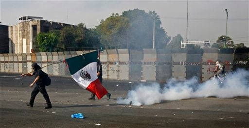© A demonstrator carrying a Mexican national flag walks past a cloud of tear gas during clashes with police outside the National Congress, just hours before Mexico's new president was to take the oath of office in Mexico City, Saturday, Dec. 1, 2012.
