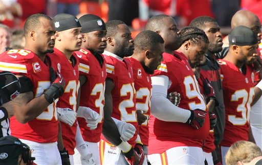 © Kansas City Chiefs players stand arm-in-arm during a moment of silence before an NFL football game against the Carolina Panthers at Arrowhead Stadium in Kansas City, Mo., Sunday, Dec. 2, 2012.