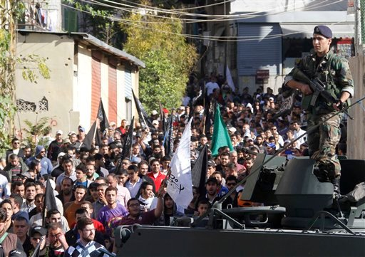 © An army soldier stands guard as supporters of Lebanese anti-Syrian regime and Salafist group leader Sheikh Ahmad al-Assir attend a protest against the Syrian regime in southern port city of Sidon, Lebanon, Sunday, Dec. 2, 2012.