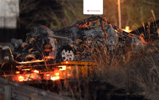 © The burnt wreckage of a minivan, which was crushed and caught fire in Sunday's accident, is moved on a transporter out of the Sasago Tunnel on the Chuo Expressway in Koshu, Yamanashi Prefecture, central Japan, early Monday, Dec. 3, 2012.