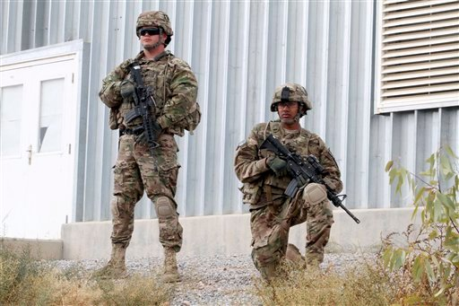 © In this Nov. 28, 2012 file photo, U.S. soldiers with stand guard as they watch the transfer ceremony of security responsibilities from NATO troops to Afghan security forces in Qalat, Zabul province south of Kabul, Afghanistan.