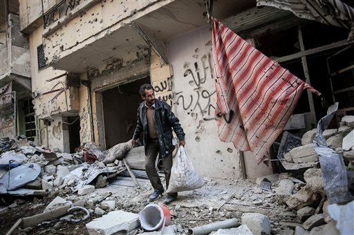 © In this Sunday, Dec. 2, 2012 photo, a man collects his belongings after his home was damaged due to heavy fighting between Free Syrian Army fighters and government forces in Aleppo, Syria.