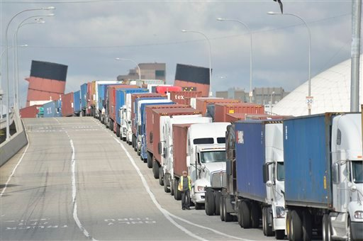 Trucks line up on Pier J Avenue. as they wait to get in to Cosco, one of the few terminals open during the clerical workers strike, in the Port of Long Beach, Calif., on Monday, Dec. 3, 2012. (AP Photo/The Daily Breeze, Jeff Gritchen)