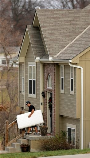 An unidentified man carries items out of a Kansas City home shared by Kansas City Chiefs linebacker Jovan Belcher and his 22-year-old girlfriend Kasandra Perkins, Monday, Dec. 3, 2012. (AP Photo/Charlie Riedel)