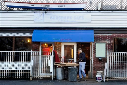 In this Dec. 4, 2012, photo, Bob Manere, owner of the Seagrape Cafe clears debris out of his bar in hopes or reopening after Superstorm Sandy in Fairfield, Conn. (AP Photo/Jessica Hill)