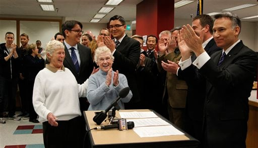 King County Executive Dow Constantine, right , leads a cheer as the clock strikes midnight and he can begin to issue marriage licenses to same-sex couples lined-up, Thursday, Dec. 6, 2012, in Seattle. (AP Photo/Elaine Thompson)