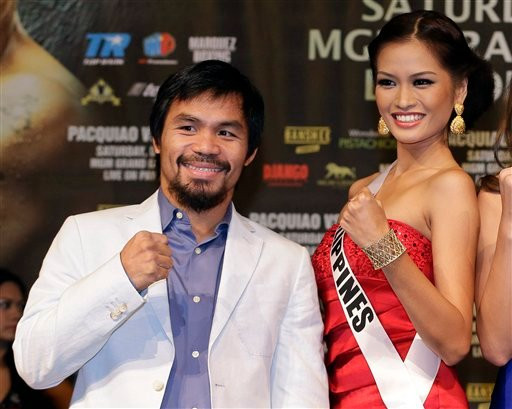 Manny Pacquiao, left, poses for photos with Miss Philippines Janine Tugonon during a news conference, Wednesday, Dec. 5, 2012, in Las Vegas.