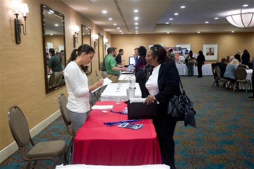 © In this Friday, Nov. 30, 2012 photo, a person fills out an application at the Fort Lauderdale Career Fair, in Dania Beach, Fla.
