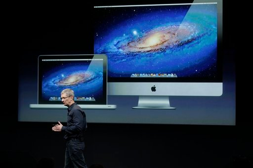 © In this Tuesday, Oct. 4, 2011, file photo, Apple CEO Tim Cook speaks in front of a projection of the Macbook Air and Mac Desktop during announcement at Apple headquarters in Cupertino, Calif.