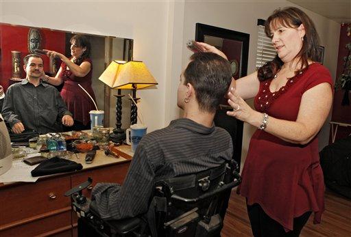 Brandon Coats' mother Donna brushes Brandon's hair at his home in Denver on Thursday, Dec. 6, 2012. (AP Photo/Ed Andrieski)