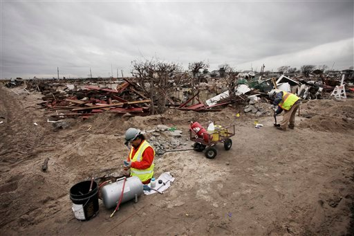 © Frank Tatulli, left, stands in a shallow pit as he installs a natural gas line in the fire-damaged zone in the Breezy Point section of New York, Friday, Dec. 7, 2012. Over 100 homes were burned to the ground during Superstorm Sandy.