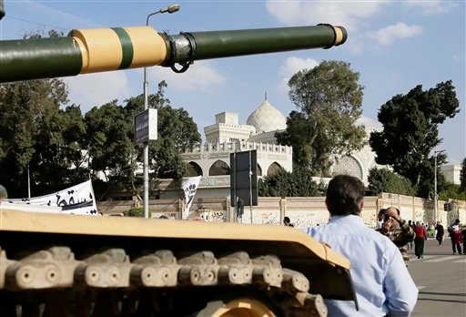© An Egyptian protester takes a picture with his mobile of another in front of an Egyptian army tank outside the presidential palace, background, in Cairo, Egypt, Saturday, Dec. 8, 2012.