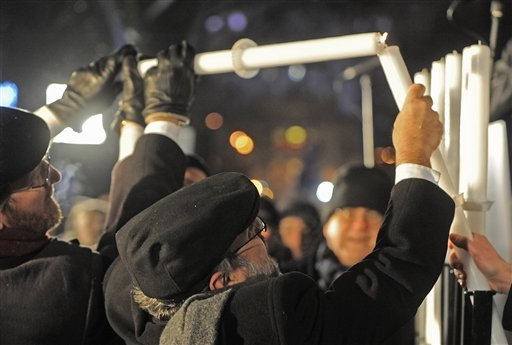 © Poland's chief rabbi Michael Schudrich, center, lights the first candle celebrating the beginning of Hanukkah, the Jewish festival of lights, on Grzybowski square in Warsaw, Poland, Saturday, Dec. 8, 2012.