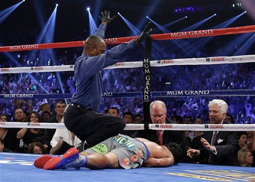  Referee Kenny Bayless calls the fight as he kneels over Manny Pacquiao, from the Philippines, after he was knocked out by Juan Manuel Marquez, from Mexico, during their WBO world welterweight fight Saturday, Dec. 8, 2012, in Las Vegas.