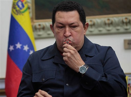 © In this photo released by Miraflores Press Office, Venezuela's President Hugo Chavez kisses a crucifix during a televised speech form his office at Miraflores Presidential palace in Caracas, Venezuela, Saturday, Dec. 8, 2012.