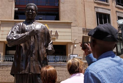 © People take photos of the giant statue of former president Nelson Mandela, in Mandela Square, Johannesburg, South Africa, Sunday Dec. 9, 2012.