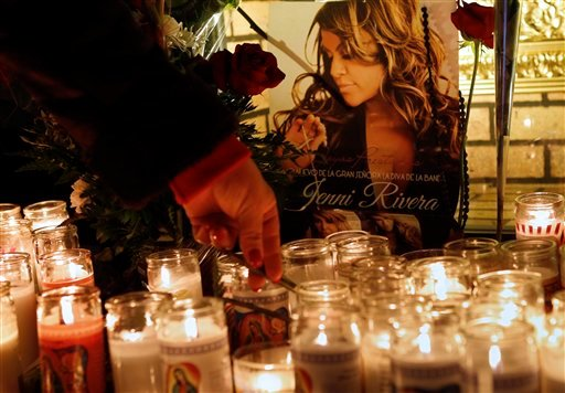  A woman adjusts a flower in front of candles and pictures displayed in tribute to singer Jenni Rivera at the Plaza Mexico shopping center in Lynwood, Calif., early Monday, Dec. 10, 2012.
