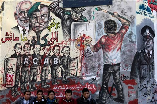 "© Egyptian boys sit in front of graffiti and Arabic, bottom. that reads, ""regime your afraid of a paint brush and a pen,"" in Tahrir Square in Cairo, Egypt,, Monday, Dec. 10, 2012."