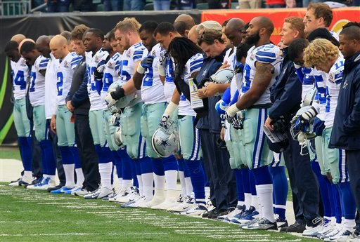 © Dallas Cowboys players hang their heads during a moment of silence honoring teammate Jerry Brown who was killed in an automobile accident prior to an NFL football game against the Cincinnati Bengals, Sunday, Dec. 9, 2012, in Cincinnati.