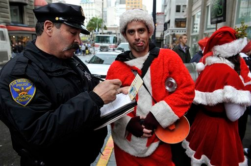FILE - This Dec. 10, 2009 file photo shows a San Francisco Police officer giving a man dressed as Santa Claus an open container ticket during the Santacon pub crawl in downtown San Francisco.  (AP Photo/Russel A. Daniels, file)