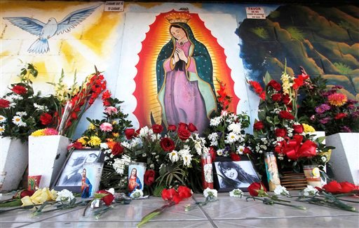 © Photos and flowers honoring late singer Jenni Rivera, placed by fans next to religious images, are seen at the cemetery where her mother is buried in Hermosillo, northern Mexico, Monday, Dec. 10, 2012.