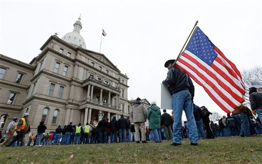© A protester holds an American flag at a rally on the State Capitol grounds in Lansing, Mich., Tuesday, Dec. 11, 2012.