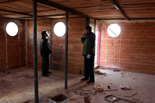 In this photo taken Nov. 24, 2012, Lu Zhenghai, right, stands inside his ark-like vessel under construction in China's northwest Xinjiang Uyghur Autonomous Region.