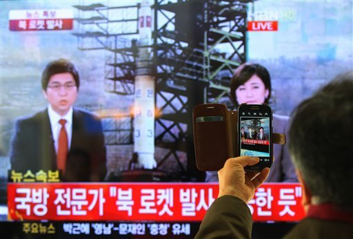 South Korean man uses his smartphone to take a television screen reporting a news about North Korea's rocket launch at Seoul Railway Station in Seoul, South Korea, Wednesday, Dec. 12, 2012. (AP Photo/Ahn Young-joon)