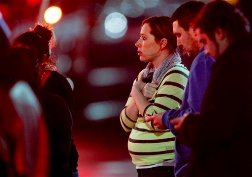 Onlookers observe the scene outside Clackamas Town Center in Portland, Ore., where a shooting occurred Tuesday, Dec. 11, 2012. (AP Photo/The Oregonian, Bruce Ely)