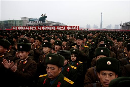 North Korean soldiers applaud near slogans honouring their leadership during a mass rally organized to celebrate the success of a rocket launch that sent a satellite into space on Kim Il Sung Square in Pyongyang, North Korea