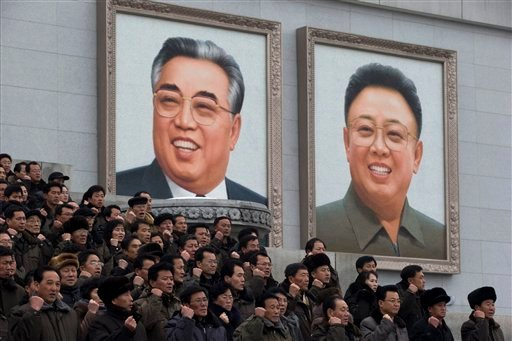 North Koreans chant slogans and gesture to show their determination near giant portraits of the late leaders Kim Il Sung, left, and Kim Jong Il during a mass rally organized to celebrate the success of a rocket launch that sent a satellite into space.