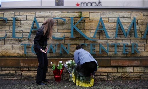 Leslie King, right and Tenille Beseda place flowers Wednesday Dec. 12, 2012, at the entrance to the scene of a multiple shooting yesterday at Clackamas Town Center Mall in Portland, Ore.