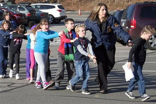 © In this photo provided by the Newtown Bee, Connecticut State Police lead children from the Sandy Hook Elementary School in Newtown, Conn., following a reported shooting there Friday, Dec. 14, 2012. (AP Photo/Newtown Bee, Shannon Hicks)