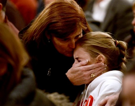 © A woman comforts a young girl during a vigil service for victims of the Sandy Hook Elementary shooting, Friday, Dec. 14, 2012, at St. Rose of Lima Roman Catholic Church in Newtown, Conn. (AP Photo/Andrew Gombert, Pool)