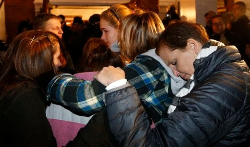 Girls embraces outside St. Rose of Lima Roman Catholic Church, which was filled to capacity, during a healing service held in for victims of an elementary school shooting in Newtown, Conn., Friday, Dec. 14, 2012. (AP Photo/Charles Krupa)