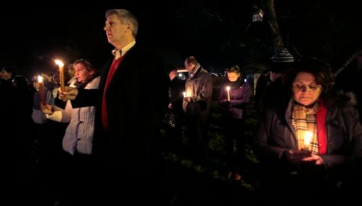 Men and women hold candles in vigil outside St. Rose of Lima Roman Catholic Church during a healing service held in for victims of an elementary school shooting in Newtown, Conn., Friday, Dec. 14, 2012.  (AP Photo/Charles Krupa)