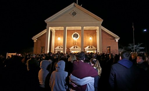 As hundreds stand outside St. Rose of Lima Roman Catholic Church, which was filled to capacity, a couple embrace during a healing service held in for victims of an elementary school shooting in Newtown, Conn., Friday, Dec. 14, 2012. (AP Photo)