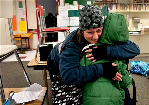 © After watching TV news reports of the school shooting in Connecticut, Alicia Combo tightly hugs her son Morgan Askins at the close of school, Dec. 14, 2012, at Garfield Elementary in Spokane, Wash.