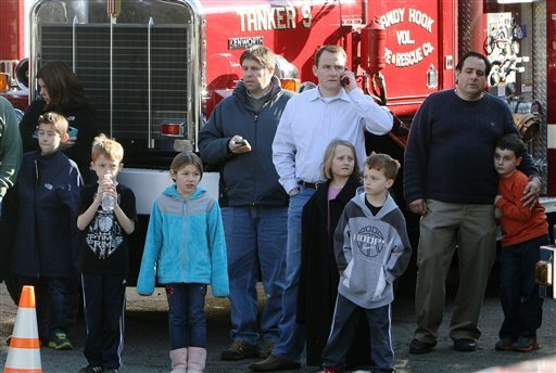© School children wait for their parents at the Sandy Hook firehouse following a mass shooting at the Sandy Hook Elementary School in Newtown, Conn. on Friday, Dec. 14, 2012. (AP Photo/The Journal News, Frank Becerra Jr.)