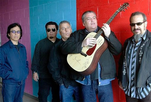 © This April 7, 2004 file photo shows members of the band Los Lobos, from left, Louie Perez, Cesar Rosas, Conrad Lozano, David Hidalgo holding a guitar, and Steve Berlin posing for a photograph, in Los Angeles.