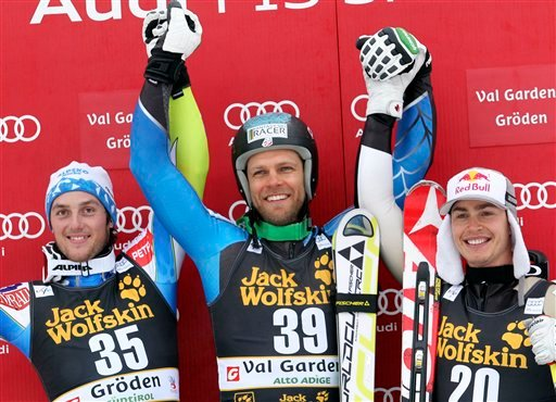© Steven Nyman, of the United States, center, winner of an alpine ski, men's World Cup downhill, celebrates on the podium with second placed Slovenia's Rok Perko, left, and third placed Canada's Erik Guay, in Val Gardena, Italy, Saturday, Dec. 15, 2012.