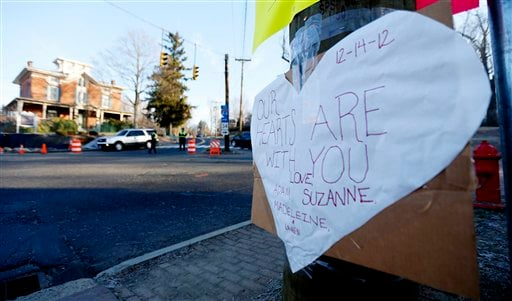  A sign on a post shows support for the victims of a gunman who opened fire inside Sandy Hook Elementary School a day earlier as police officers stand at a road block, Saturday, Dec. 15, 2012, in Sandy Hook village of Newtown, Conn.