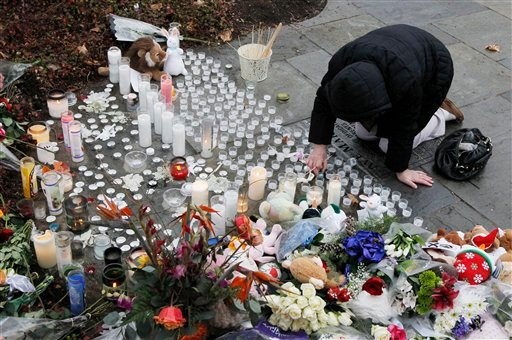 © A woman pays respects at a memorial outside of St. Rose of Lima Roman Catholic Church, Sunday, Dec. 16, 2012, in Newtown, Conn.