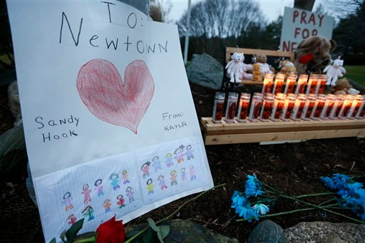 © A child's message rests with a memorial for shooting victims, Sunday, Dec. 16, 2012, in Newtown, Conn. A gunman walked into Sandy Hook Elementary School in Newtown on Friday and opened fire, killing 26 people, including 20 children.