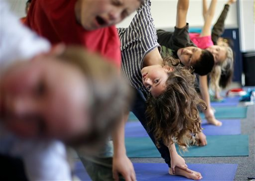 © In this Dec. 11, 2012 picture, fourth grader Anna De La Fuente reaches holds a position during a yoga class at Capri Elementary School in Encinitas, Calif.