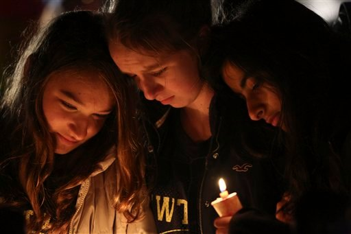© Kate Suba, left, Jaden Albrecht, center, and Simran Chand pay their respects at one of the makeshift memorials in honor of the victims of the Sandy Hook Elementary School shooting, Sunday, Dec. 16, 2012, in Newtown, Conn.