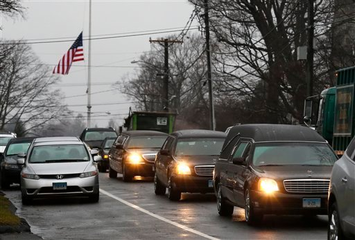 A hearse and family limousines for six-year-old shooting victim Jack Pinto rolls past a flag at half staff as the funeral procession heads through the historic district in Newtown, Conn., Monday, Dec. 17, 2012. (AP Photo/Charles Krupa)